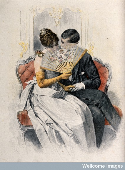 A young couple sit on a sofa holding hands while she coyly holds a fan up to her face. Coloured wood engraving by Rud. Rössler. Wellcome Images
