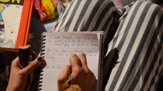 Hannah writes in her diary during her performance piece.