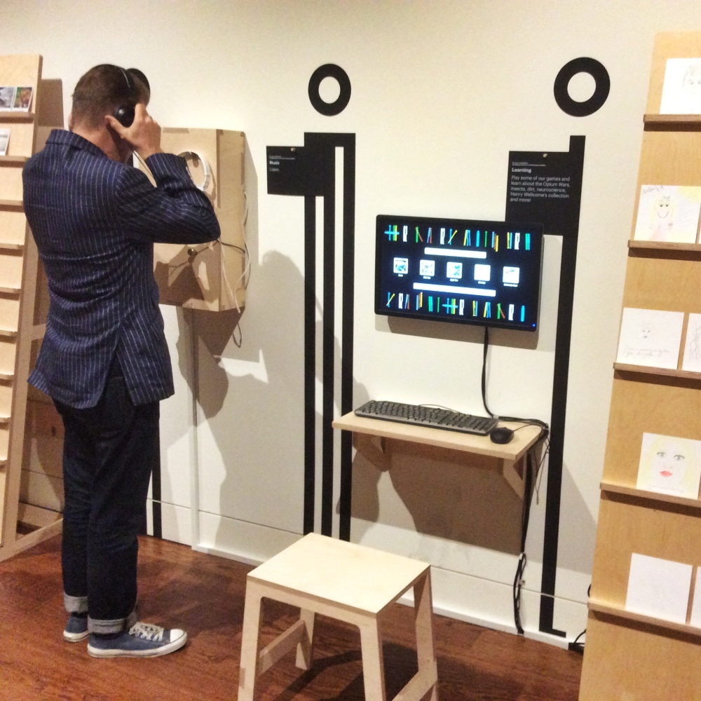"""A visitor listening to some music on the """"For your contribution"""" side of the exhibition, featuring listening stations and digital games."""