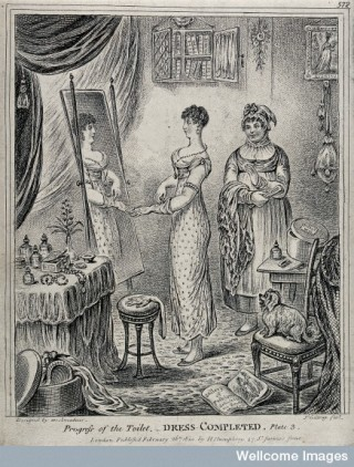 A woman in evening dress standing in front of a mirror.