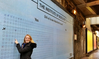 Emily standing in front of our interactive Sexology posters in Shoreditch.