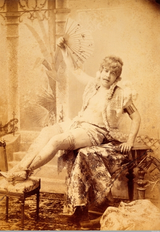 L0031642 PP/KEB/E/6/4, Man seated, wearing ladies shoes and stockings