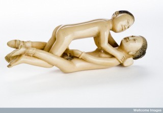 Chinese statue of a man and woman engaged in sexual foreplay.