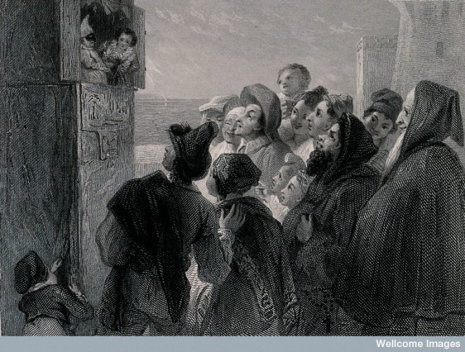 A crowd of people have gathered around a stand in the street to watch a Punch and Judy show.
