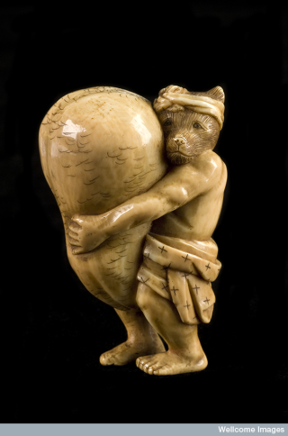 Could you be inspired by the history of this netsuke, a mischievous racoon dog who carries his own enlarged scrotum?