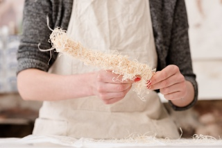 She moulds the wood wool around wire to make the body shape.