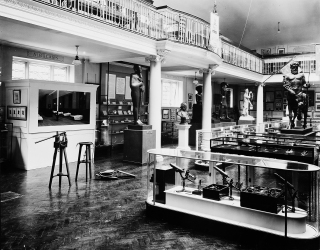 Wellcome's Medical Historical museum at Wigmore Street. Lister pump, diorama and microscopes in the foreground.